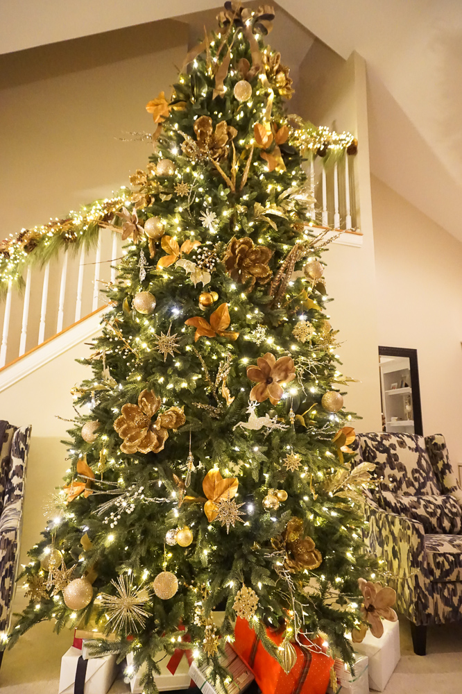 Blogger Authentically Emmie shares her Christmas tree decor, including a 12 foot gold magnolia themed tree, and long pine needle garland. #christmas #christmastree
