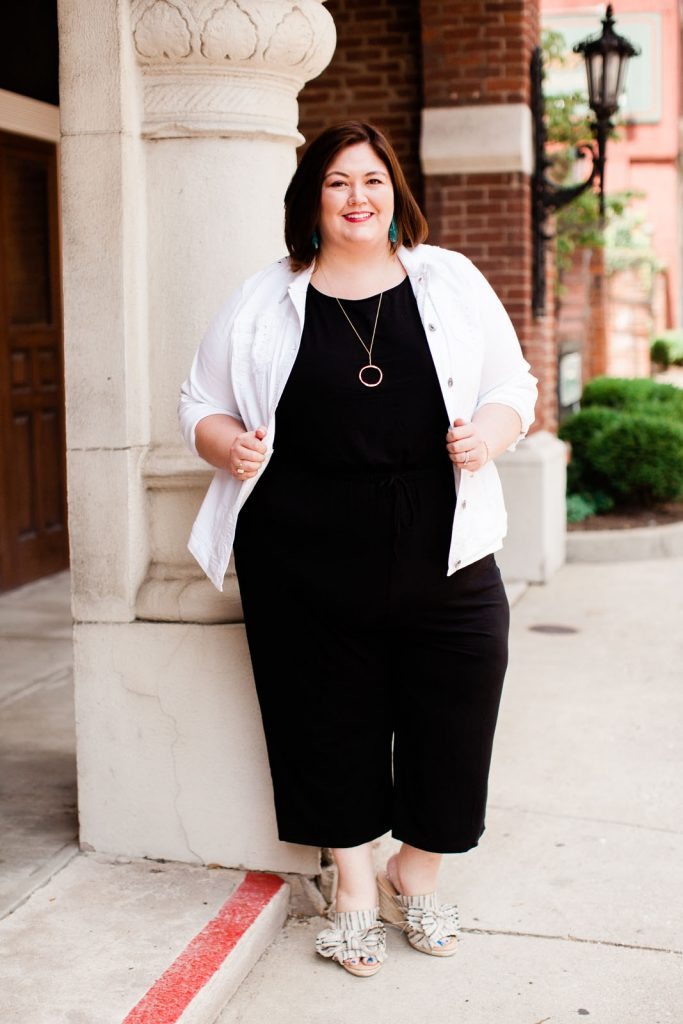 Plus size fashion blogger Authentically Emmie in a Catherines jumpsuit with denim jacket