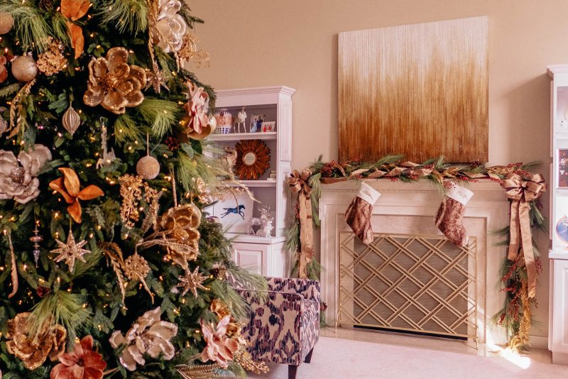 Gold magnolia themed Christmas tree and fireplace mantel decoration