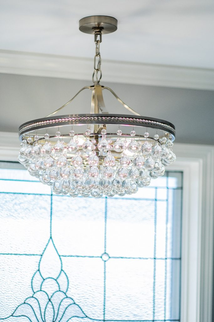 Crystal and nickel chandelier from Lamps Plus above a master bathroom bathtub