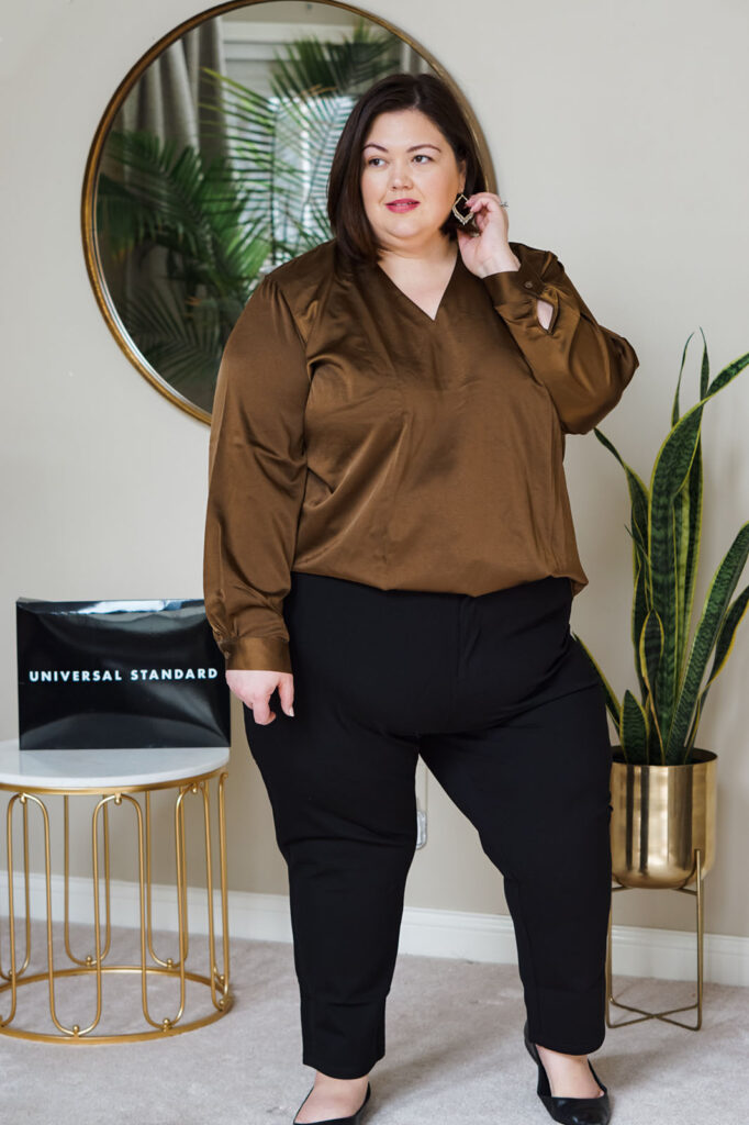 Plus size outfit for work, featuring a professional satin top and black cigarette pant trousers.